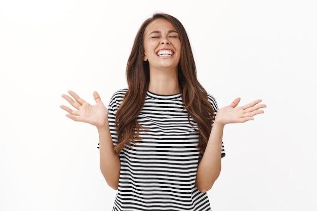 Garota, graças a deus por ter ganhado, sentindo-se feliz por receber notícias fantásticas e inacreditáveis, aliviada alegre mulher entusiasmada levantando a cabeça, fecha os olhos e sorrindo, levanta as mãos agradecida, ganhando na loteria