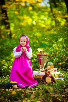 Garota gracinha em um xale rosa e vestido, uma jaqueta branca como masha e o urso do desenho animado.