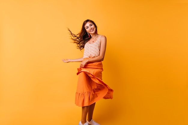 Garota graciosa brincando com sua saia de verão brilhante. retrato interior de mulher jovem e relaxada dançando no estúdio.