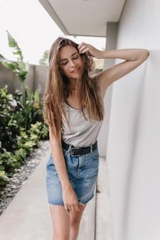 Garota graciosa em saia jeans, posando com os olhos fechados perto de uma parede branca. retrato ao ar livre de uma adorável senhora morena em pé perto da casa com arbustos