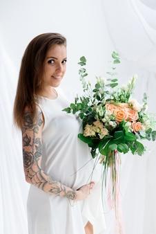 Garota grávida feliz em um vestido branco.