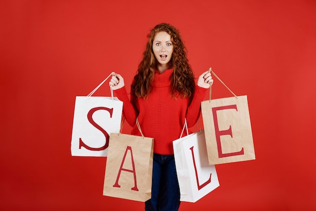 Garota gritando com sacolas de compras em estúdio