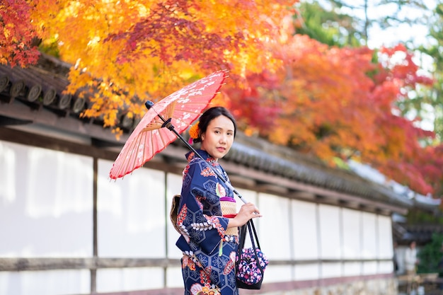 Garota gueixa vestindo quimono japonês entre tori gate de madeira vermelha no santuário de fushimi inari em kyoto,