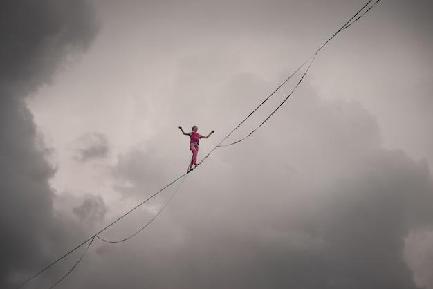 Garota highliner no fundo de um céu nublado