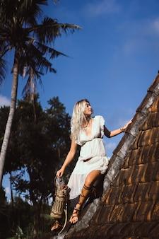 Garota hippie com longos cabelos loiros em um vestido no telhado.