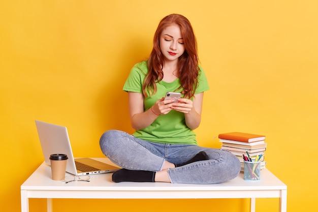 Garota hippie se senta em uma mesa branca e usa um smartphone para comunicação online
