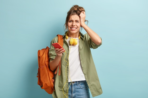 Garota hipster estressada e insatisfeita com dor de cabeça depois de ouvir música alta em fones de ouvido por muito tempo, segura um celular moderno