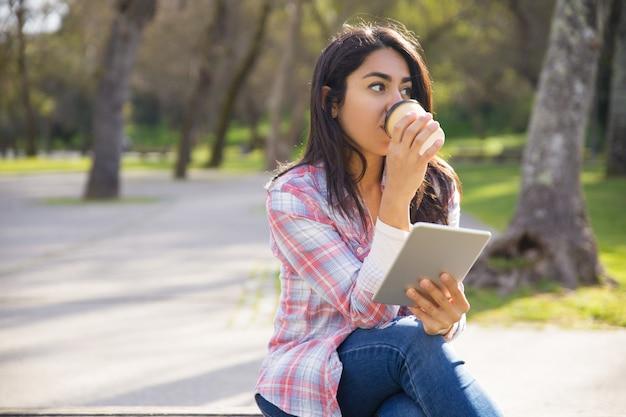 Garota hipster pacífica, desfrutando de ebook e café da manhã no parque