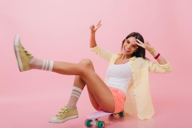 Garota hispânica entusiasmada na jaqueta amarela da moda sentada no longboard com as pernas para cima. mulher latina alegre em pulseiras coloridas rindo