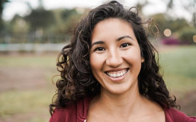 Garota hispânica sorrindo para a câmera ao ar livre no parque da cidade