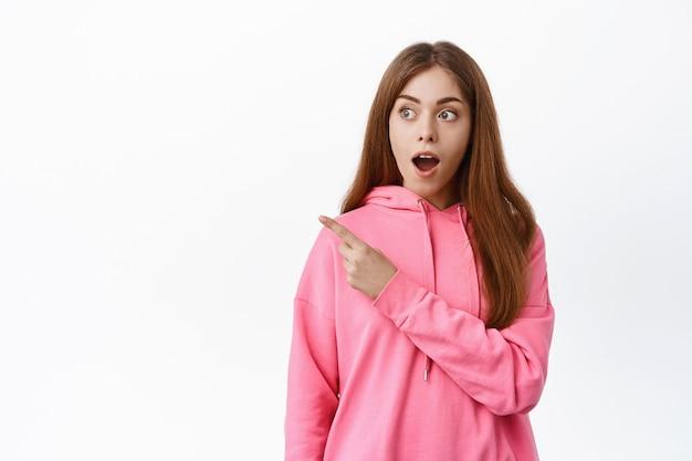 Garota impressionada, ofegando, apontando e olhando para o lado esquerdo no espaço da cópia, mostra uma promoção incrível, encostada na parede branca