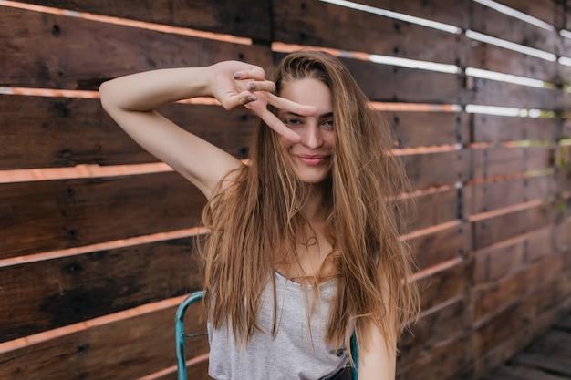 Garota incrível com cabelo castanho, posando com símbolo da paz, em um bom dia de primavera. tiro ao ar livre do feliz modelo feminino caucasiano rindo na parede de madeira.