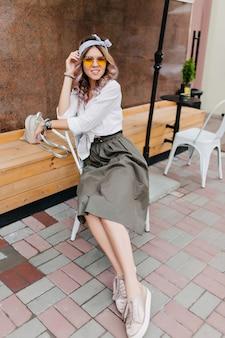Garota incrível com camisa clássica e tênis relaxando em um café ao ar livre e posando em pose confortável