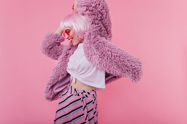 Garota incrível com jaqueta roxa se divertindo durante a sessão de fotos interna. linda modelo feminina de óculos escuros e peruca rosa dançando e rindo