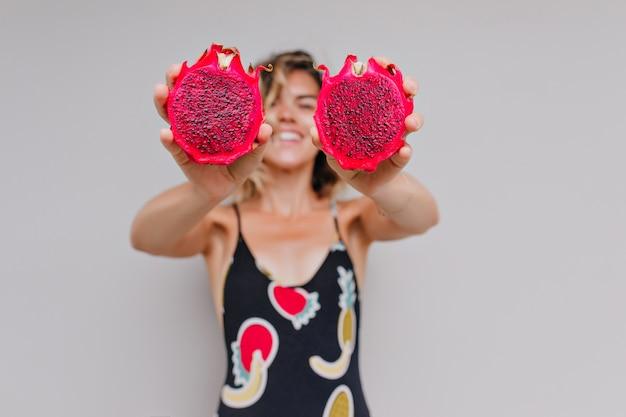Garota incrível com pele bronzeada segurando pitaiaiás vermelha e rindo. retrato de mulher sorridente refinada com frutas exóticas nas mãos.