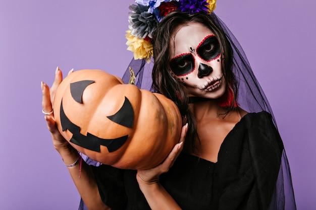 Garota incrível com véu de noiva preto isolado na parede roxa. foto interna da senhora malvada em traje de zumbi segurando abóbora de halloween.