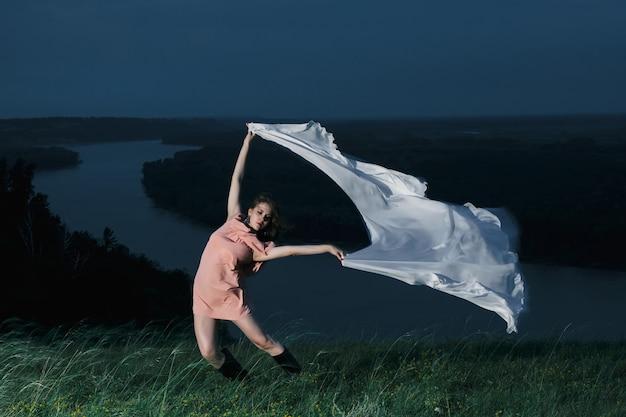 Garota incrível dançando no vestido rosa com grande xale branco à noite
