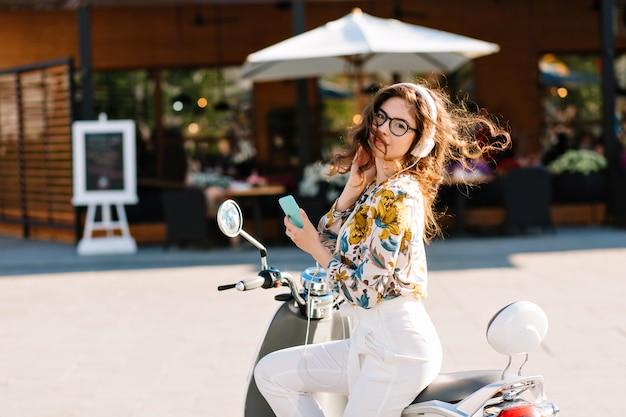 Garota incrível e elegante com telefone na scooter esperando o namorado que foi tomar um café no café