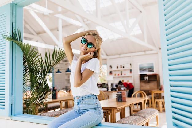 Garota incrível em calças casuais vintage, sentado no parapeito da janela com um sorriso. foto de mulher loira romântica em copos brilhantes, tocando sua cabeça.