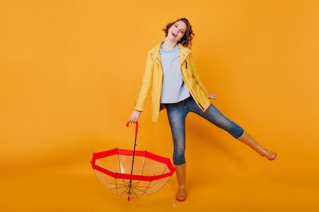 Garota incrível em jeans azul e camisa engraçada dançando, segurando guarda-chuva e sorrindo. senhora alegre no casaco de outono e sapatos de borracha, se divertindo depois da chuva.