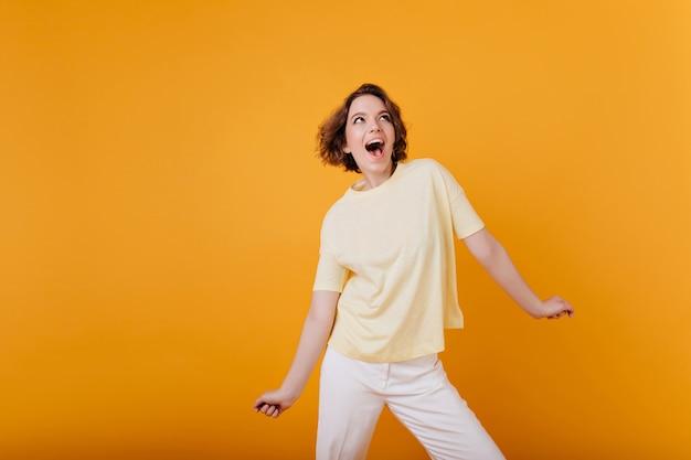 Garota incrível rindo com tatuagem posando na parede laranja brilhante. linda senhora europeia em roupa casual da moda.