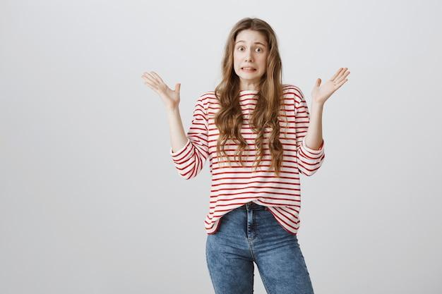 Garota indecisa e preocupada levantando as mãos confusa