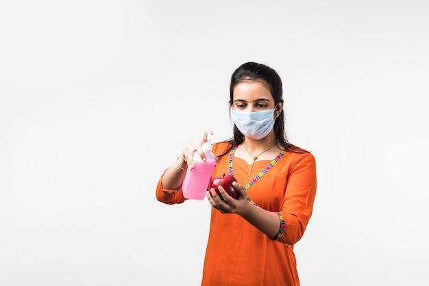 Garota indiana bonita usa máscara facial. sanitizando maçã ou aplicando desinfetante em frutas