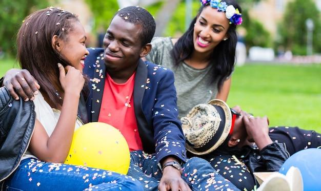 Garota indiana e casal africano comemorando juntos na festa de rua