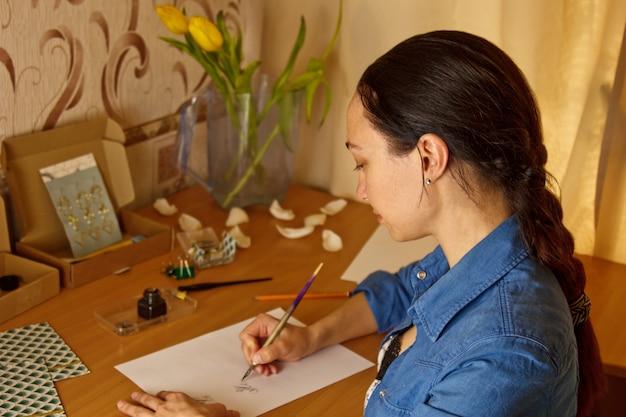 Garota indiana escreve com caneta de tinta em uma folha de papel branco.