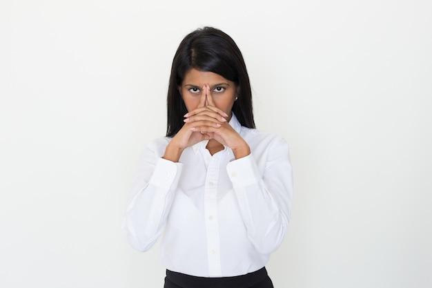 Garota indiana séria posando com as mãos entrelaçadas no rosto