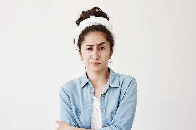 Garota infeliz séria vestindo trapo em cabelos escuros ondulados tem expressão atraente, carrancas enfrentam em insatisfação.