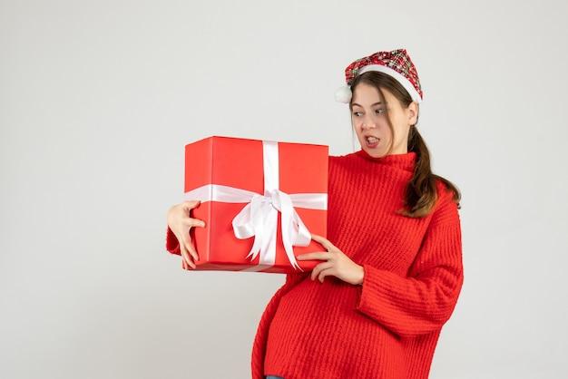 Garota insatisfeita com um chapéu de papai noel segurando um presente de pé