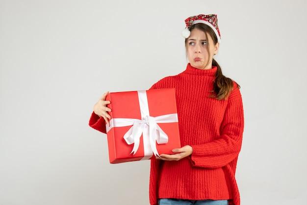 Garota insatisfeita de frente com chapéu de papai noel segurando um presente com as duas mãos