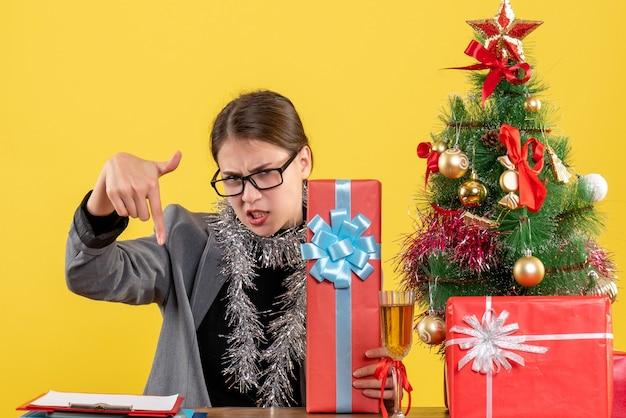 Garota insatisfeita de frente com óculos sentada à mesa apontada com o dedo para baixo da árvore de natal