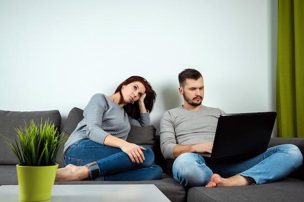 Garota insatisfeita olha para um cara jogando em um laptop