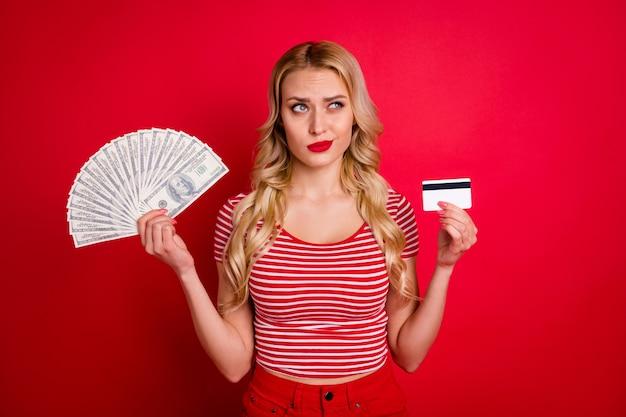Garota insegura segurar dinheiro fã cartão de crédito decidir escolher olhar copyspace