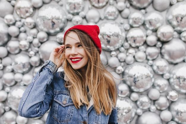 Garota inspirada com cabelos castanhos lisos, olhando para longe com um sorriso durante a sessão de fotos com acessórios de festa. foto de uma linda mulher europeia com chapéu vermelho em pé perto de bolas de discoteca.