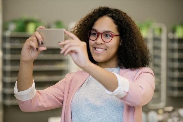 Garota intercultural feliz usando óculos segurando o smartphone na frente do rosto enquanto experimenta novos óculos e faz selfie