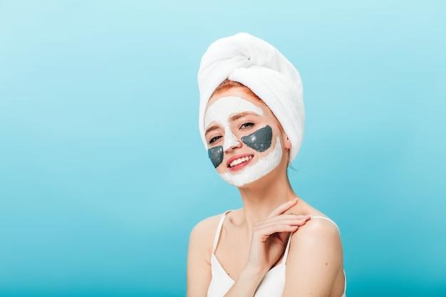 Garota interessada com máscara facial, olhando para a câmera. foto de estúdio de senhora bem-humorada com uma toalha na cabeça, fazendo tratamento para a pele.