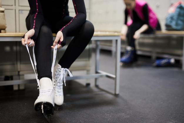 Garota irreconhecível, amarrando patins de gelo