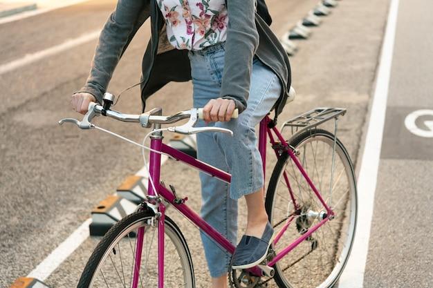 Garota irreconhecível com bicicleta na ciclovia