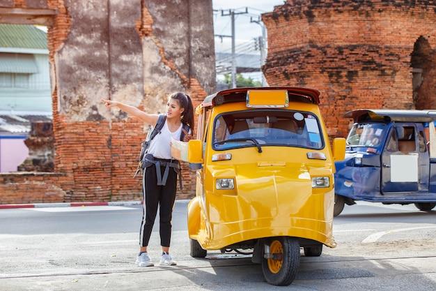 Garota japonesa viajante segurando o mapa de consulta de viagem para o caminho com motorista táxi
