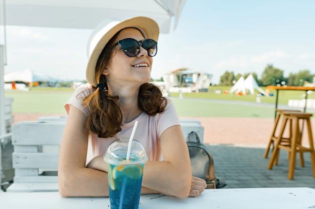 Garota jovem adolescente em óculos de sol chapéu sorrindo e bebendo coquetel de frutas legal