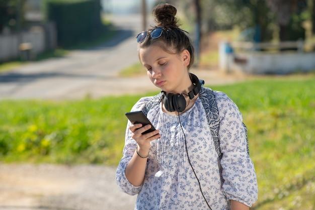 Garota jovem adolescente esperando o ônibus escolar e usando seu smartphone