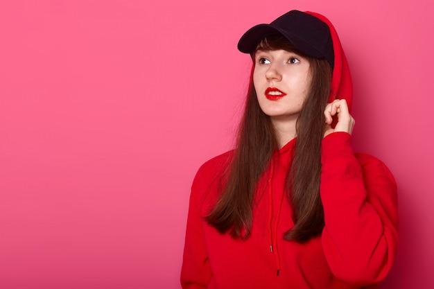 Garota jovem adolescente morena bonito casual capuz vermelho e boné, posando com listick brilhante na rosa, olhando de lado no espaço da cópia. publicidade e conceito de pessoas.