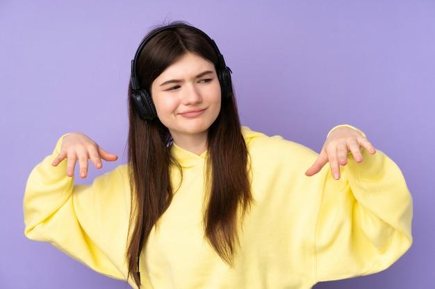 Garota jovem adolescente sobre parede roxa, ouvir música e dançar