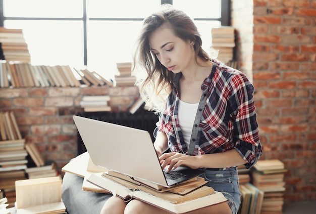 Garota jovem adolescente usando o computador portátil, rodeado por muitos livros.