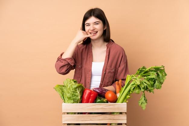 Garota jovem agricultor com legumes recém colhidos em uma caixa fazendo gesto de telefone