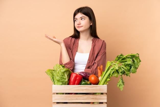 Garota jovem agricultor com legumes recém colhidos em uma caixa infeliz por não entender algo