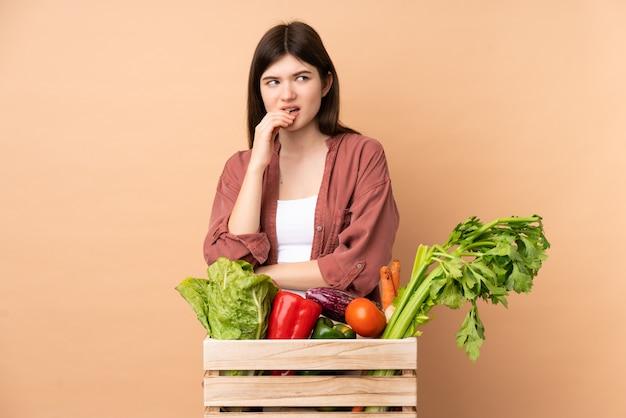 Garota jovem agricultor com legumes recém colhidos em uma caixa nervosa e assustada